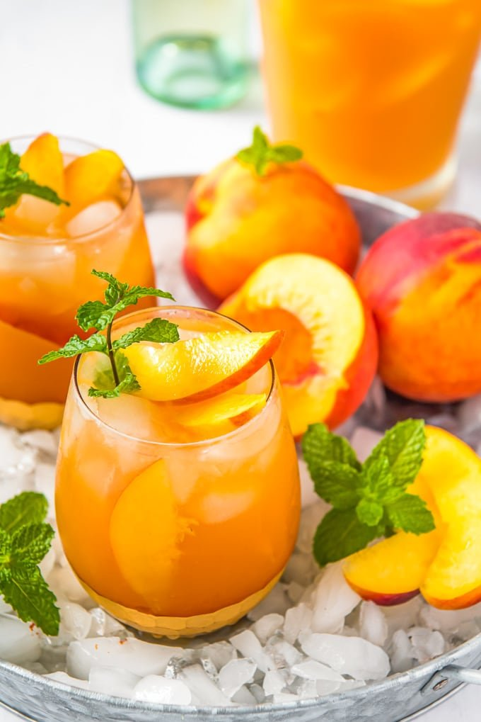 An overhead image of a glass of peach sangria, plus a pitcher and some fresh peaches and crushed ice.