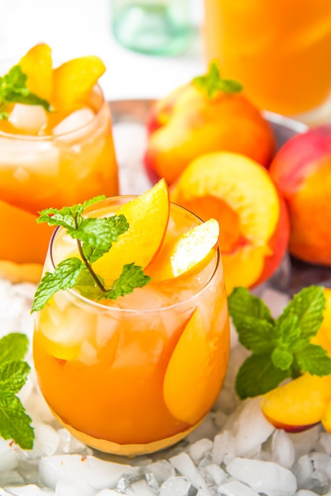Two glass of peach sangria with crushed ice and fresh peaches