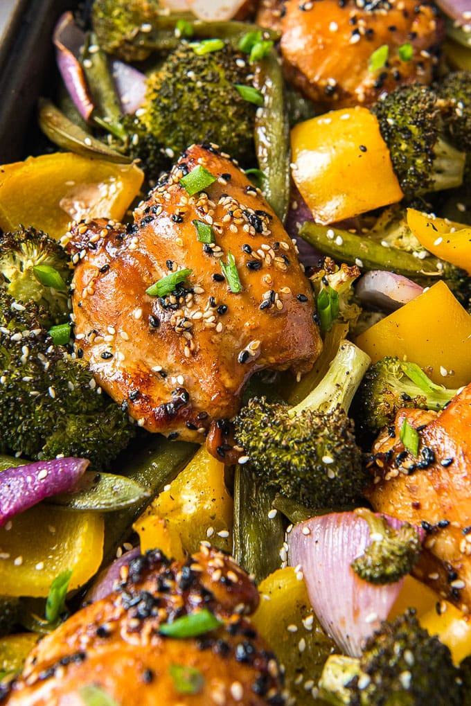 A close up of a chicken thigh with sesame chicken marinade and vegetables.