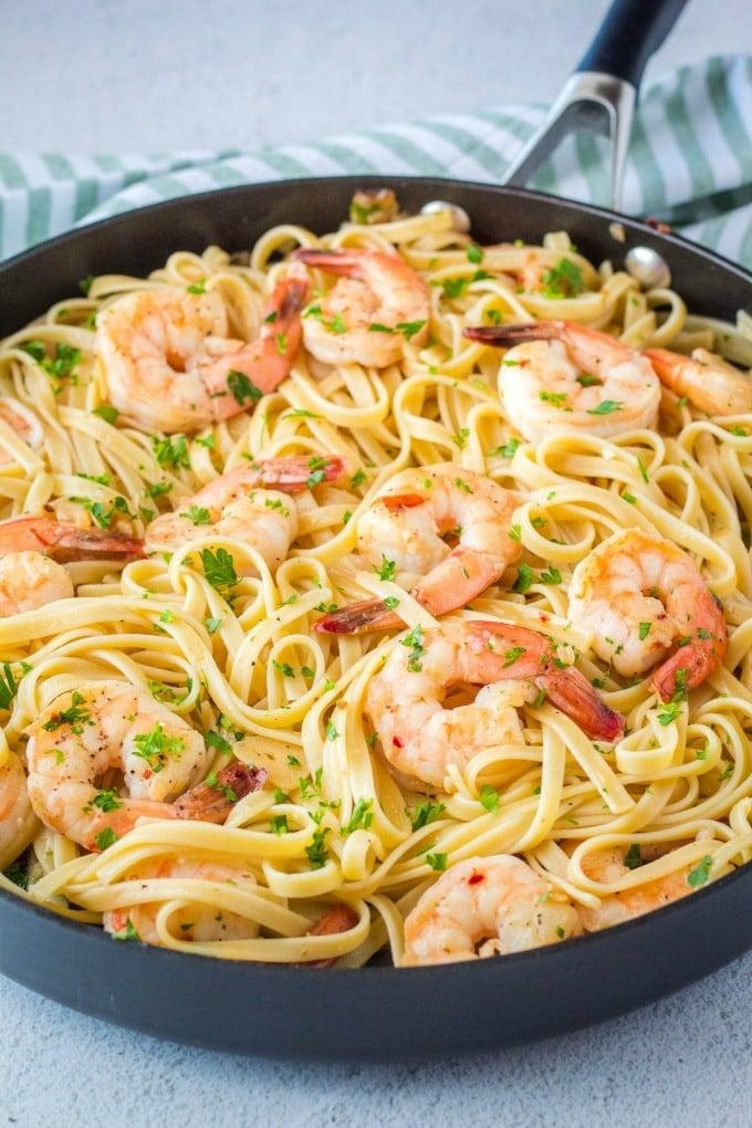shrimp scampi in a skillet with pasta