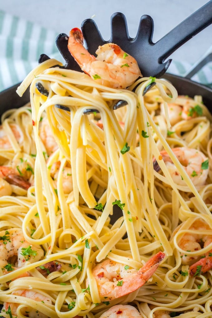 pasta spoon lifting a serving of shrimp scampi pasta from a pan