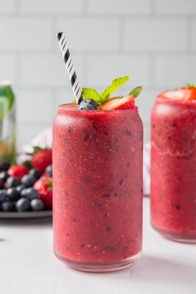 A close up image of a skinny berry smoothie in a glass with a can of diet 7up and fresh berries in the background.