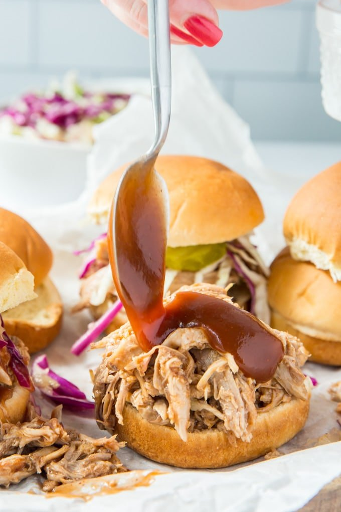Half of a slider roll topped with pulled pork with a spoon spreading bbq sauce on top