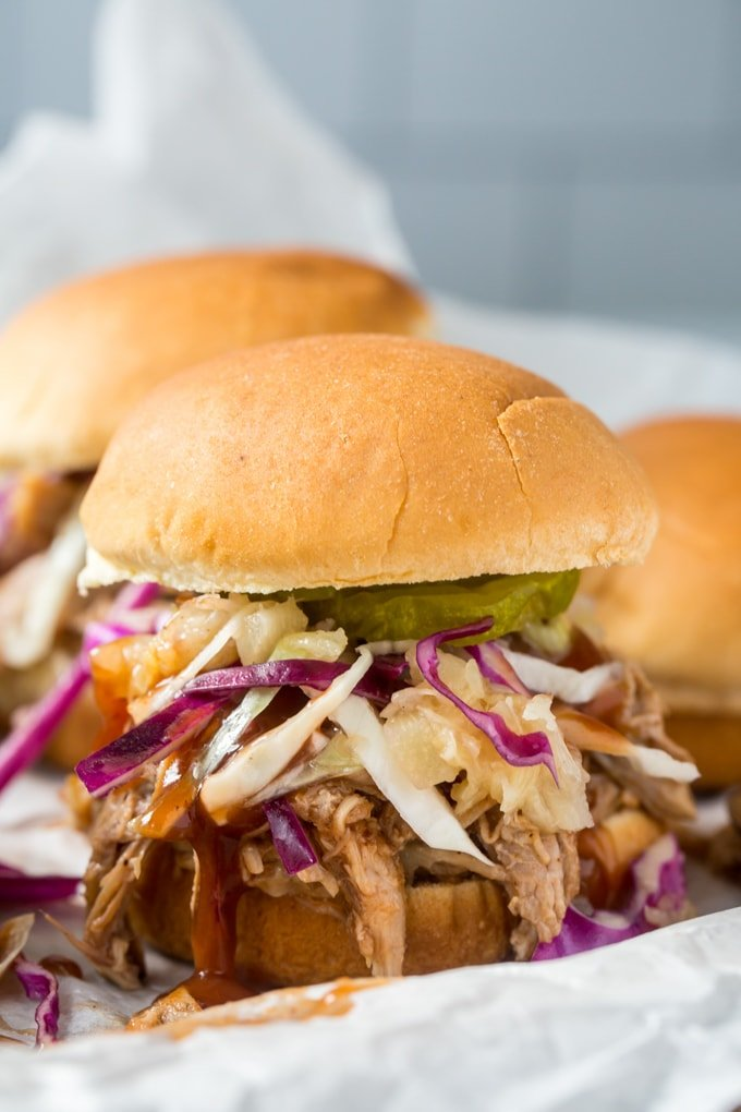 A close up image of a pulled pork slider with coleslaw and pickles