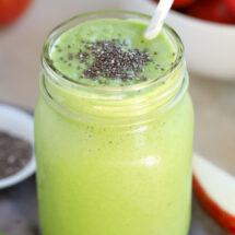 A green smoothie topped with chia seeds in a mason jar.