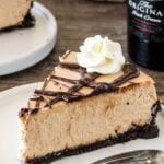 A slice of extra creamy Baileys cheesecake with an Oreo crust and chocolate ganache.
