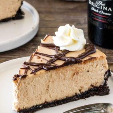 A slice of extra creamy Baileys cheesecake with an Oreo crust and chocolate ganache.