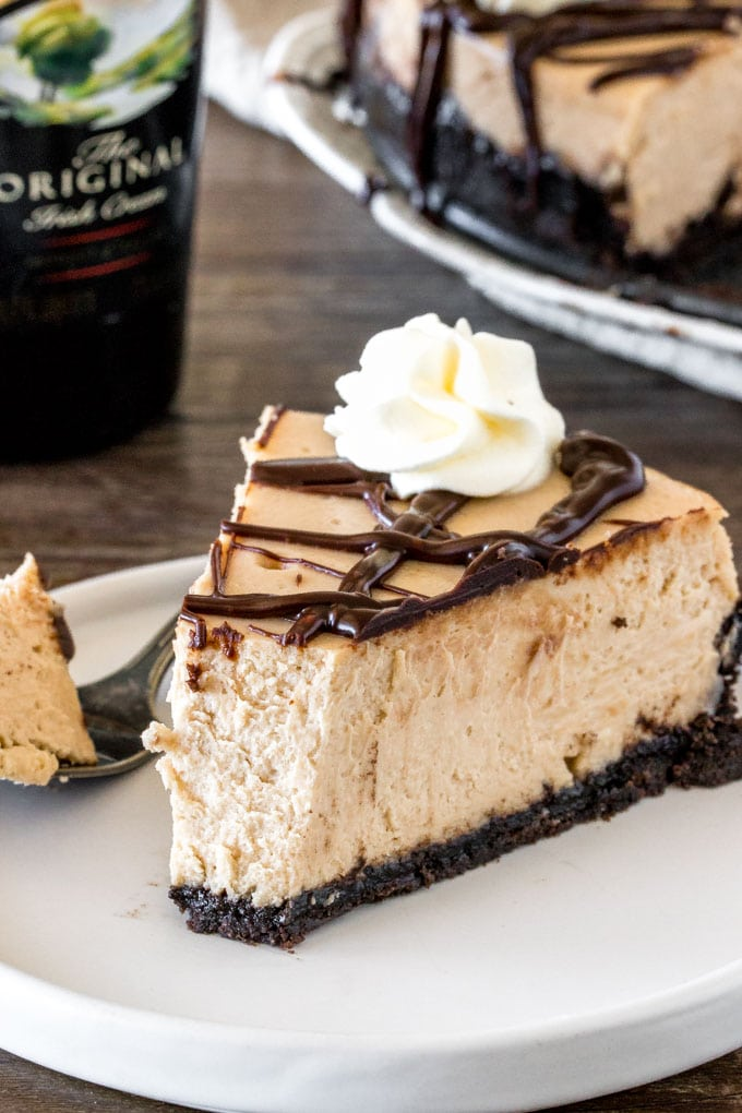A slice of Irish cream cheesecake with a bite take out of it to show the creamy texture.