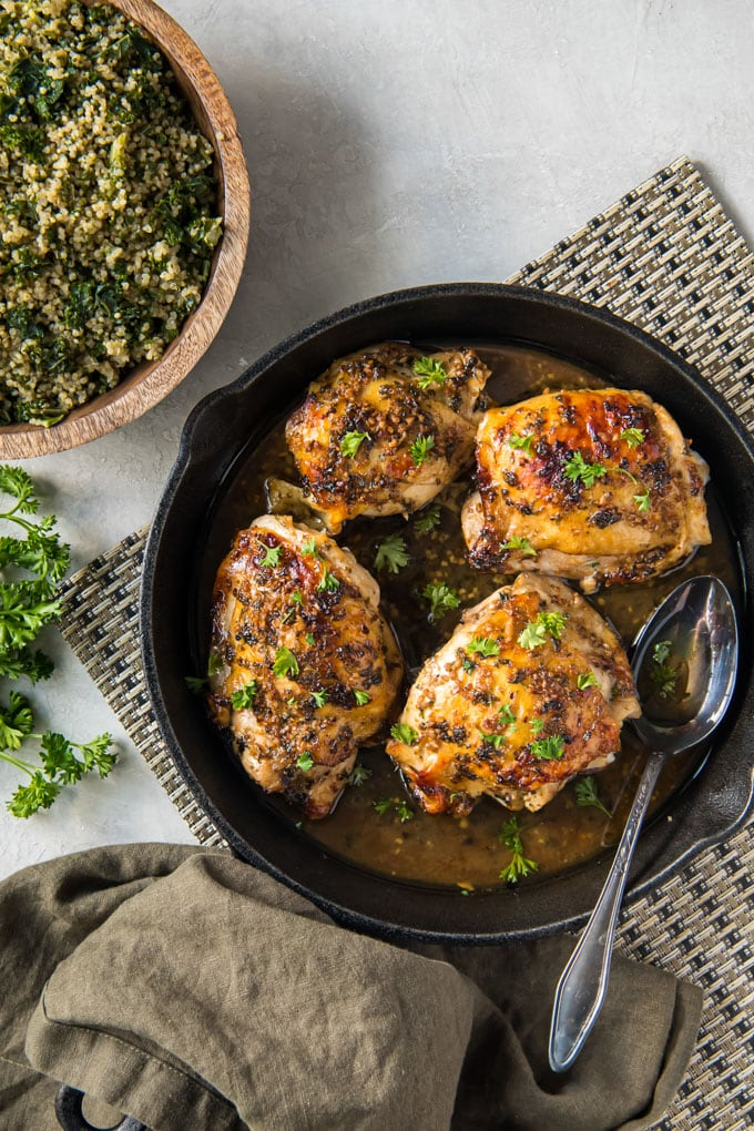 cast iron skillet, 4 roasted chicken thighs, silver spoon, bowl of quinoa