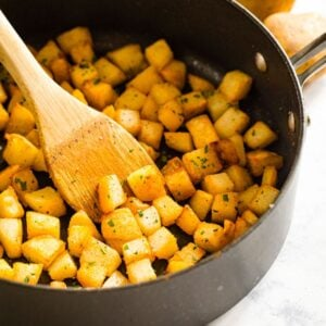 black saute pan with diced potatoes and parsley, wooden spoon.