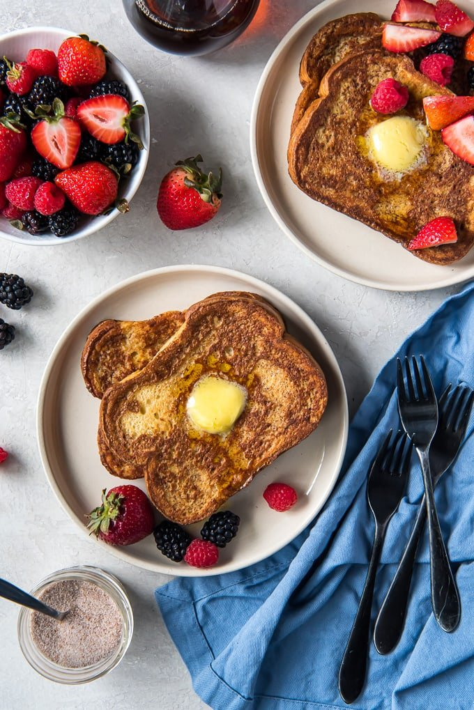 Two plates with french toast stacked with berries, a blue napkin and three forks.