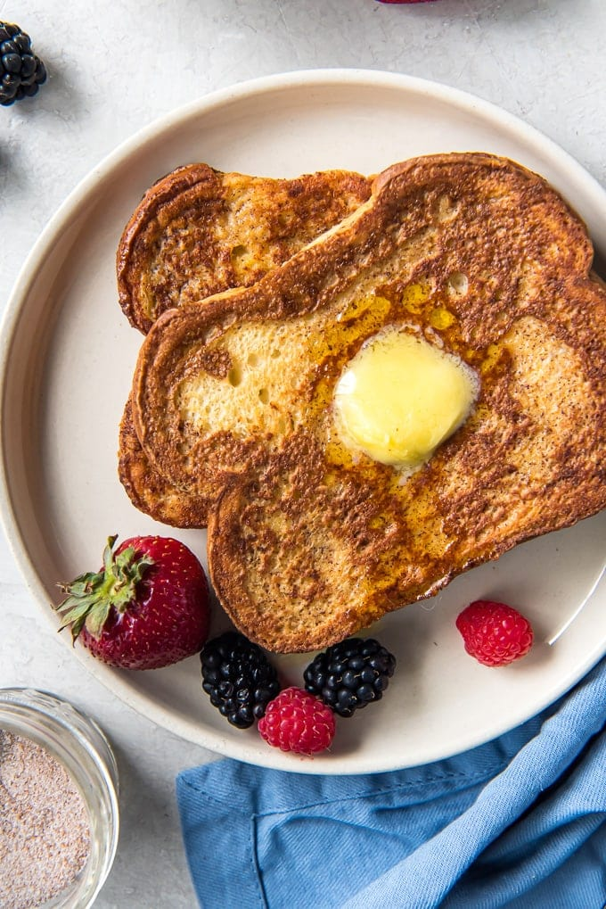Two slices of french toast, stacked on a plate with fresh berries