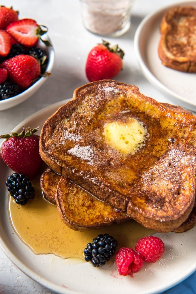 A plate with french toast, fresh berries and maple syrup.