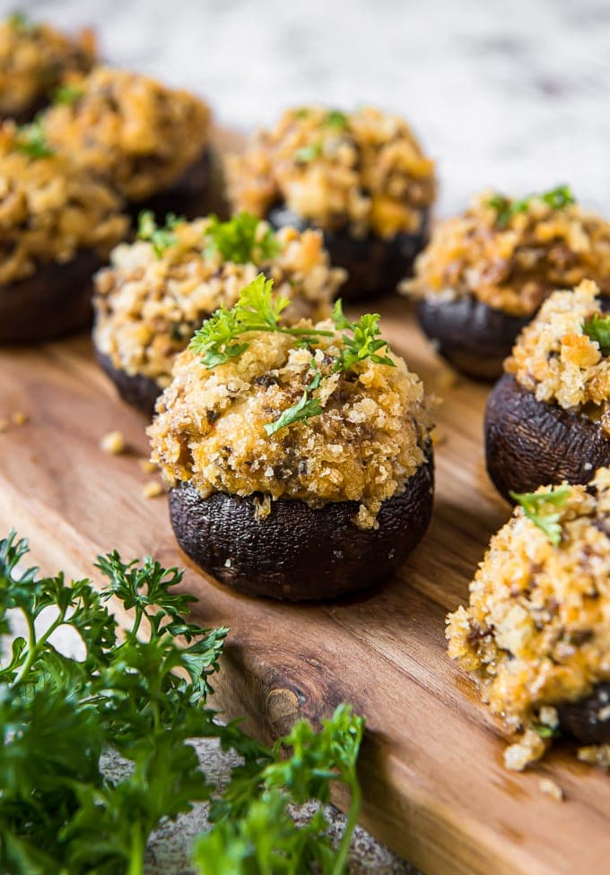 A close up of a stuffed mushroom with sausage and cheese filling and topped with parsley.