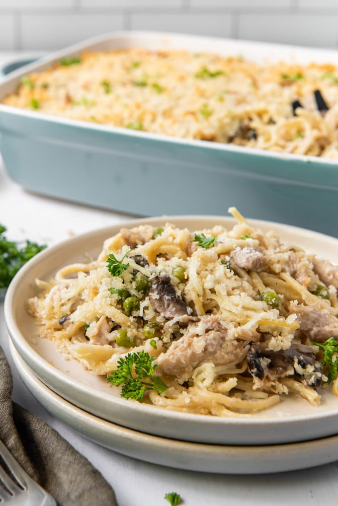 Turkey tetrazzini pasta with vegetables with a serving on a plate and the rest ina casserole dish