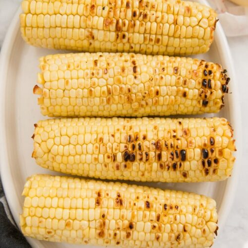 4 ears of grilled corn on the cob on a white plate. Image for social media.