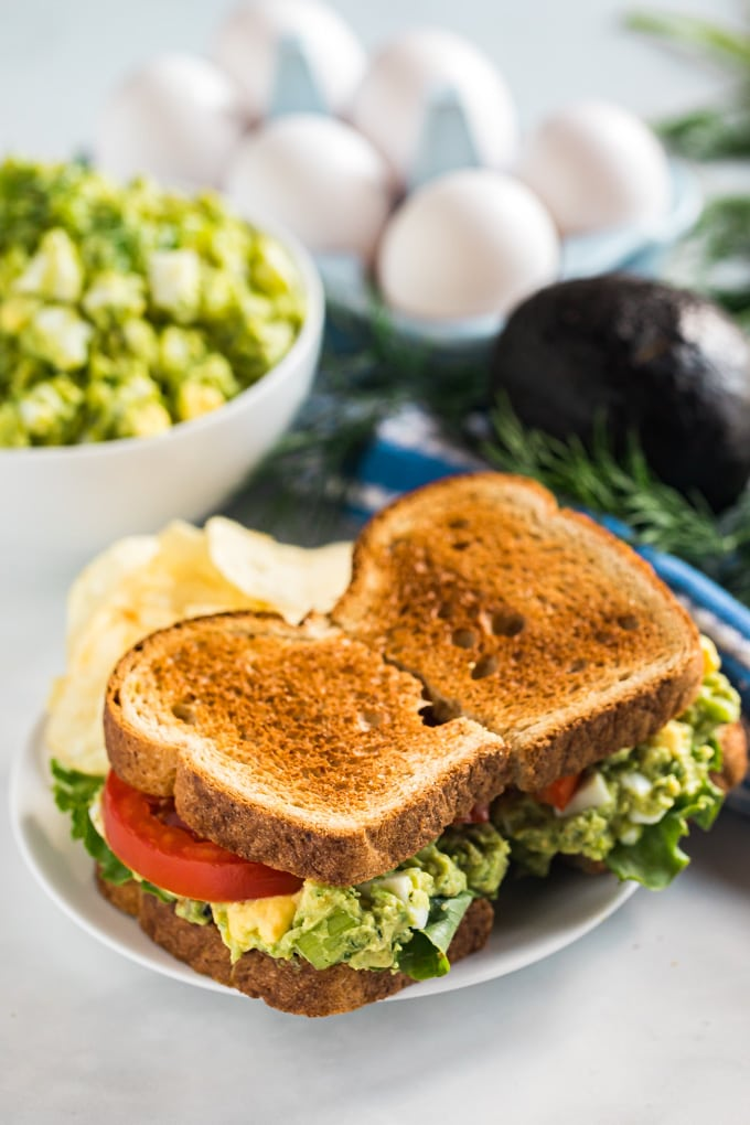 An avocado egg salad sandwich on a plate with chips.