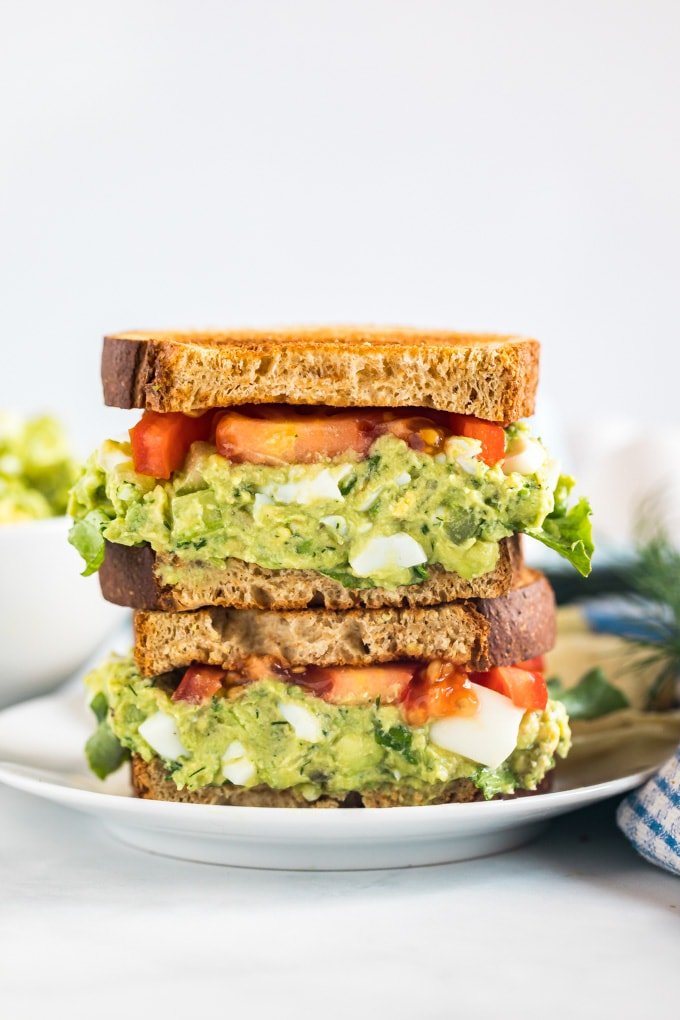 Two halves of an avocado egg salad sandwich stacked on top of each other revealing the center.
