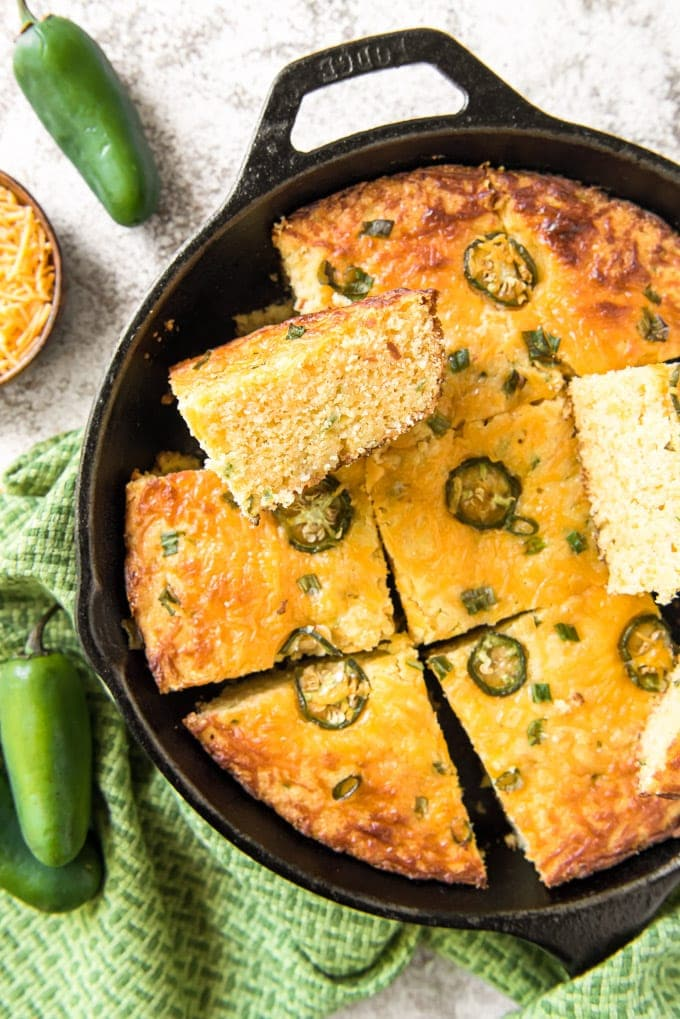 Cornbread with jalapenos in a skillet, sliced, with some pieces on their sides.