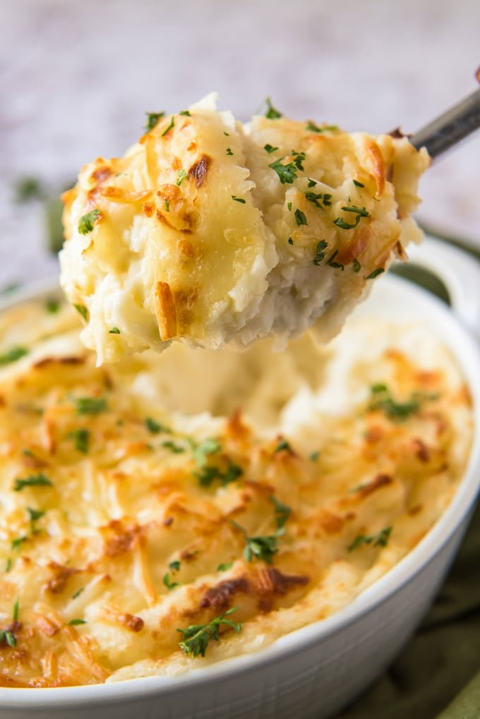 A large spoon scooping out a serving of cheesy mashed potatoes