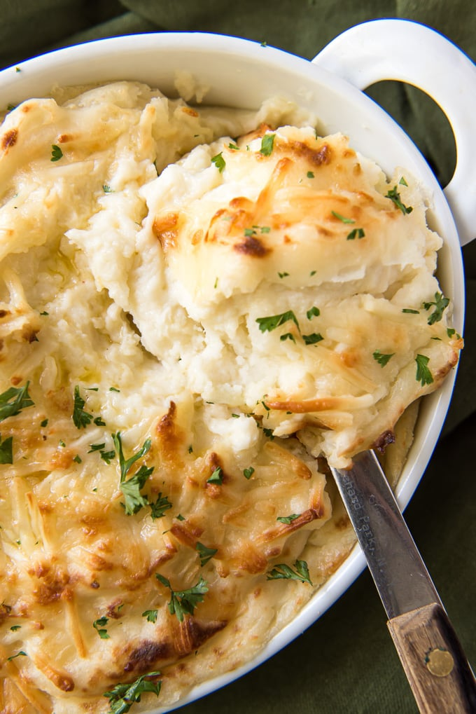 A large spoon with a scoop of cheesy mashed potatoes sitting on the dish