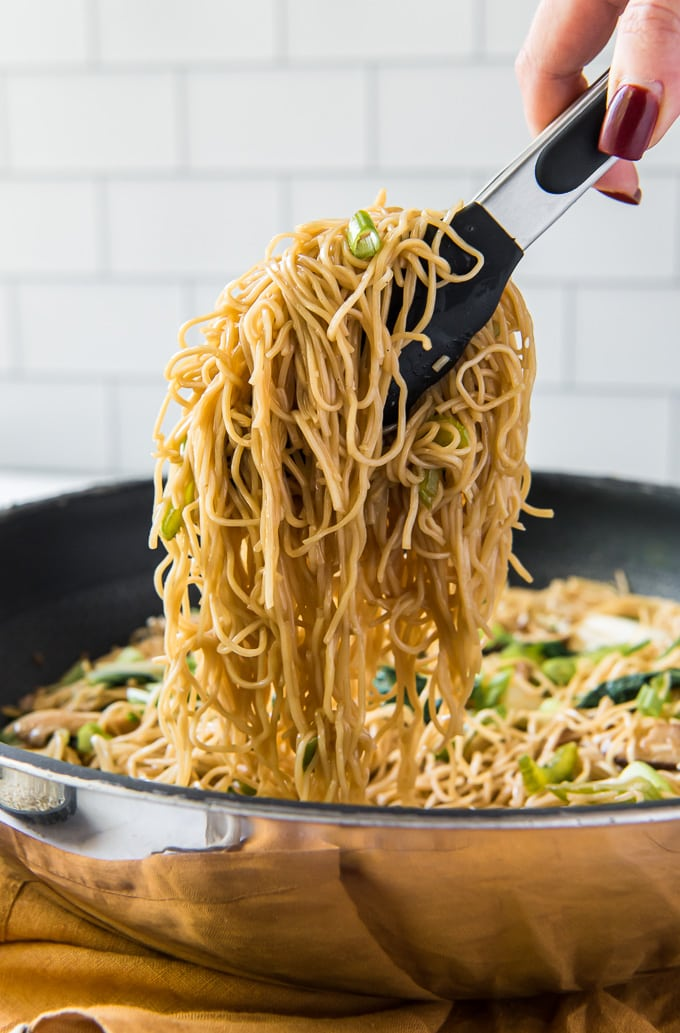 Chow mein noodles lifted out of the pan with tongs.