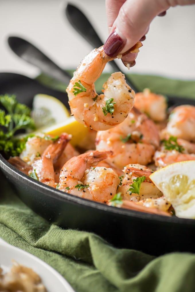 A plate of garlic shrimp with parsley and lemon