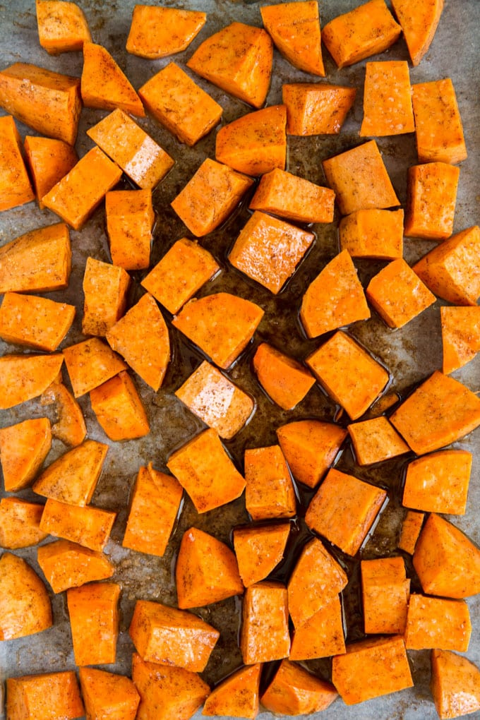 Cut up chunks of sweet potatoes on a sheet pan