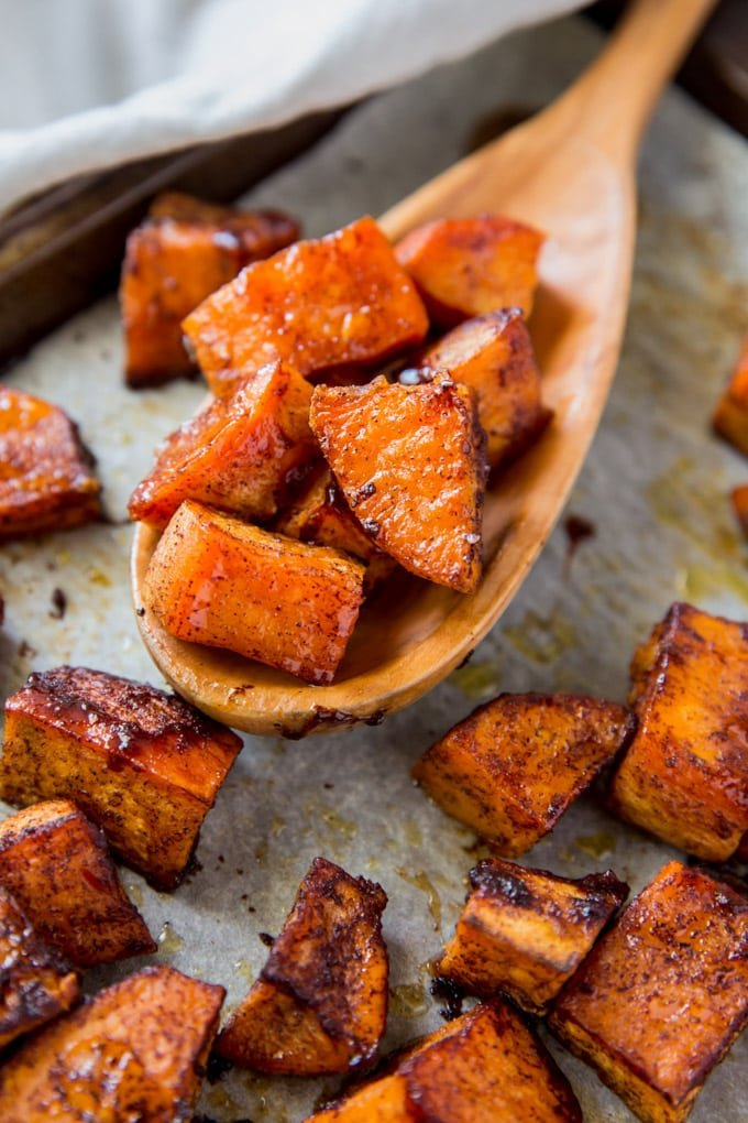 A close up of roasted sweet potatoes on a wooden spoon