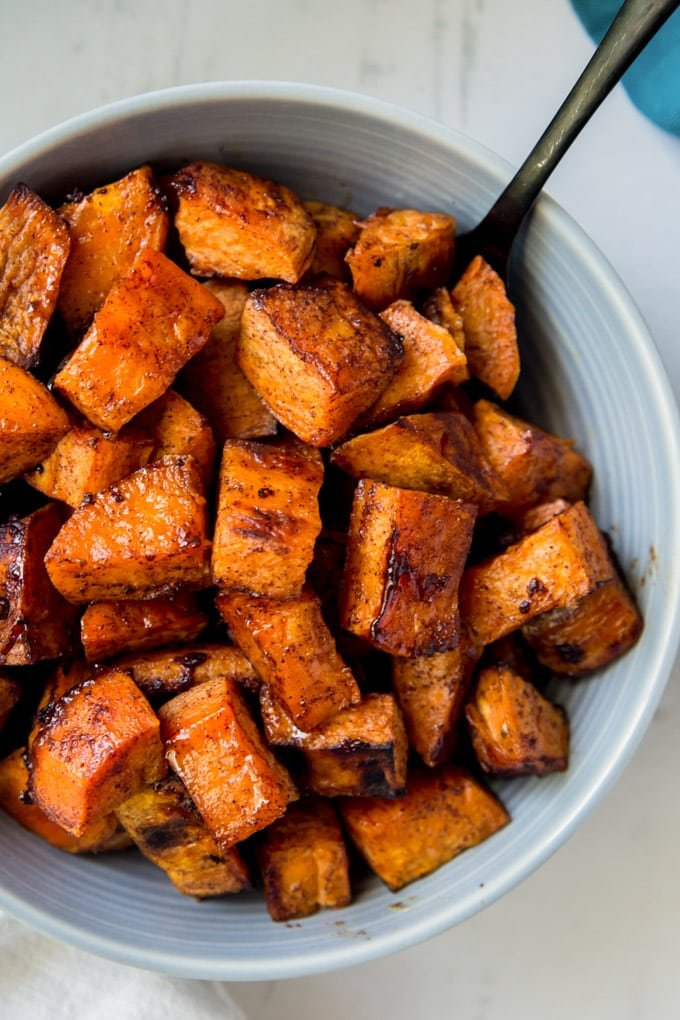 A bowl of roasted sweet potatoes with cinnamon and honey