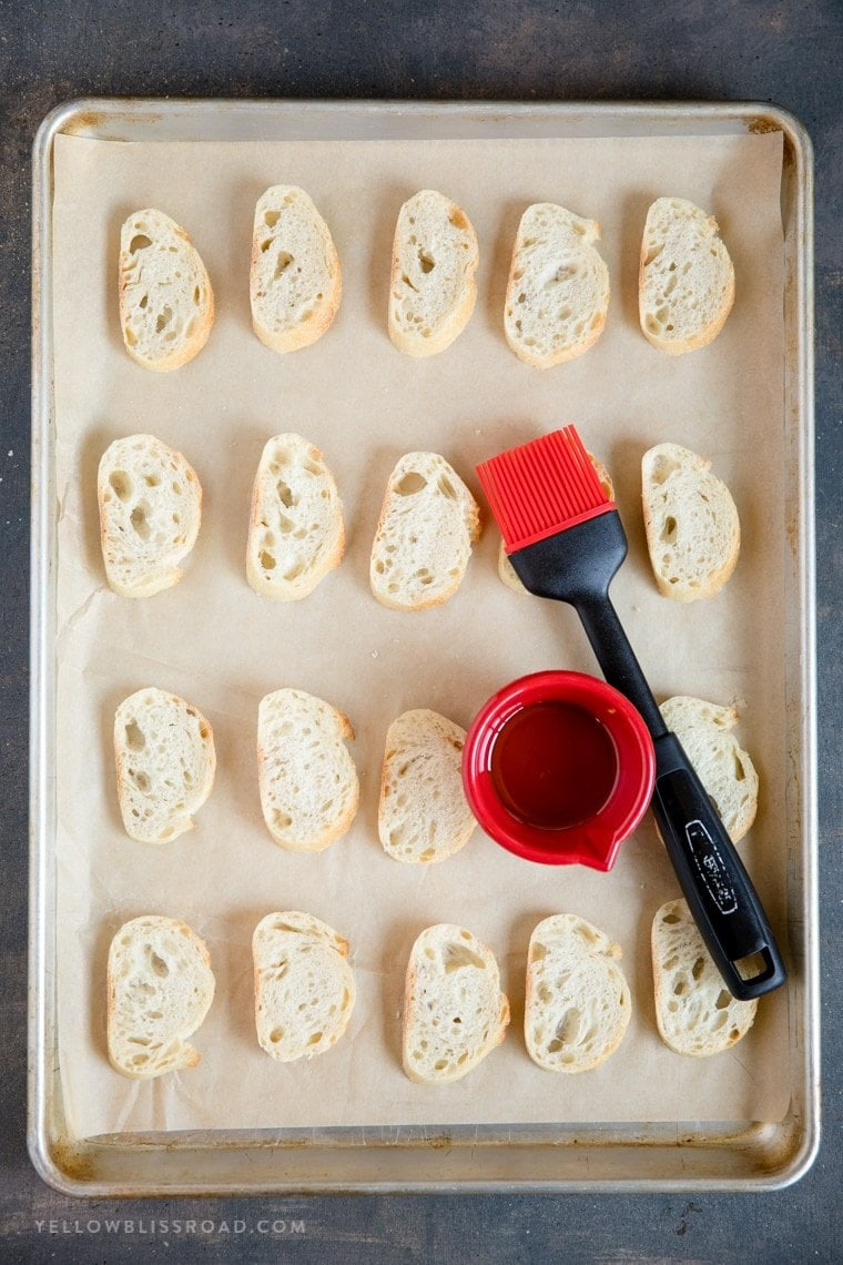 A sheet pan with slices of bread and a pastry brush and bowl of olive oil