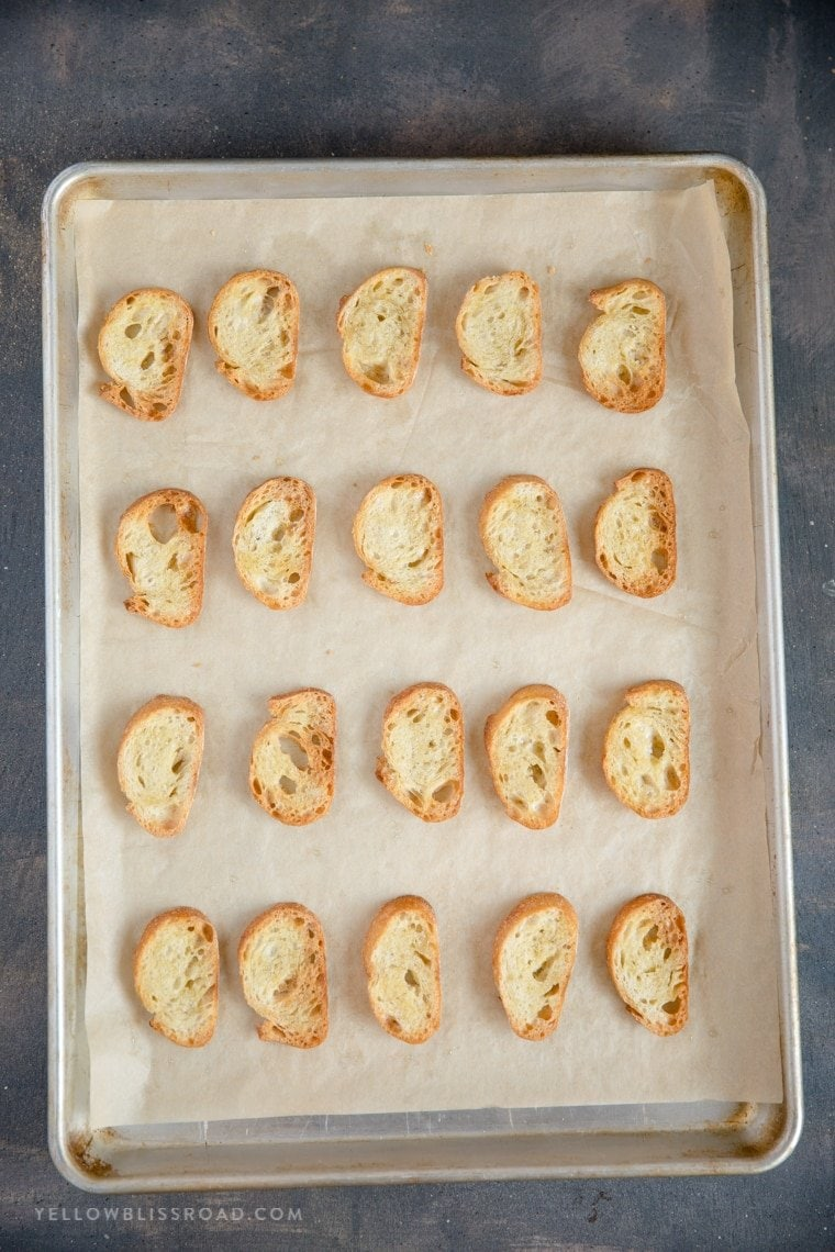 Crostini slices laid out on a parchment paper covered baking sheet.