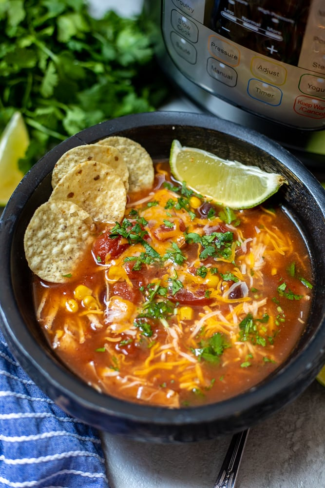 Instant Pot Chicken Tortilla Soup in black bowl next to Instant Pot