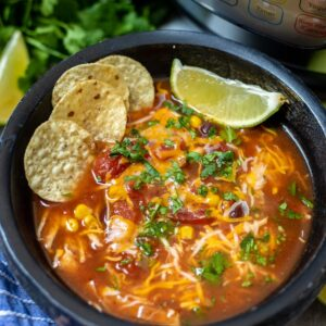 Bowl of Instant Pot Chicken Tortilla Soup topped with corn chips and fresh lime