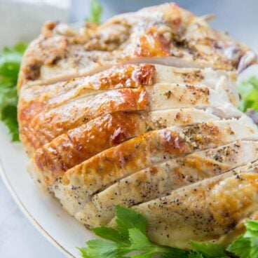 Turkey breast, browned skin, sliced and sitting on top of large pieces of parsley. Image for social media.