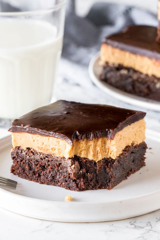 A layered peanut butter brownie with a bite taken out of it.
