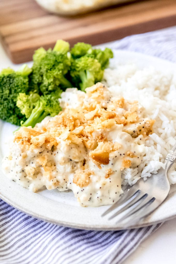 An image of poppy seed chicken casserole on a plate with broccoli and rice.
