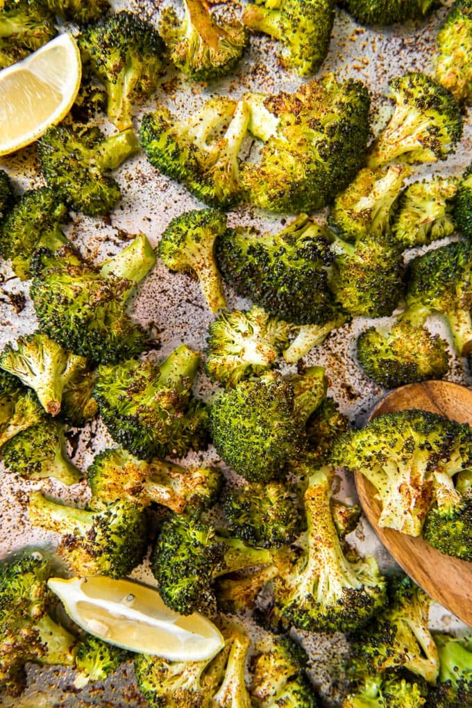 An overhead shot of roasted broccoli and lemon wedges on a sheet pan.