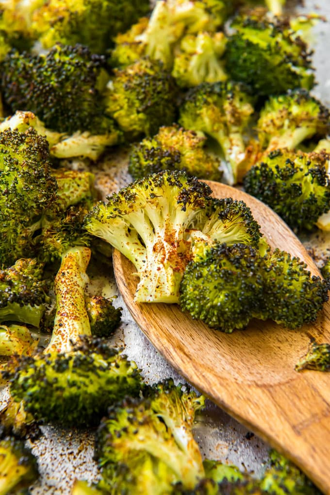 A wooden spoon holding a couple of pieces of roasted broccoli on a sheet pan