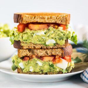 A close up of a plate of avocado egg salad sandwich