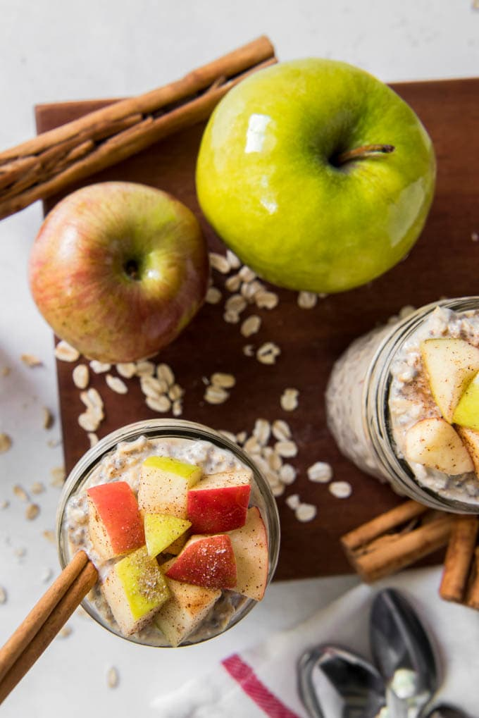 Two jars of Apple Cinnamon Overnight Oats with apples sitting on a table