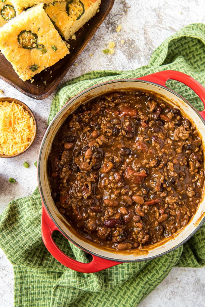 A pot of the best over chili sitting on a green towel next to a plate of cornbread