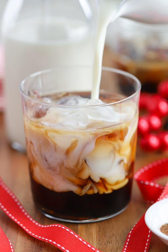 Eggnog being poured into a white russian cocktail.