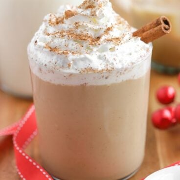 Eggnog White Russian Cocktail topped with whipped cream and a cinnamon stick.