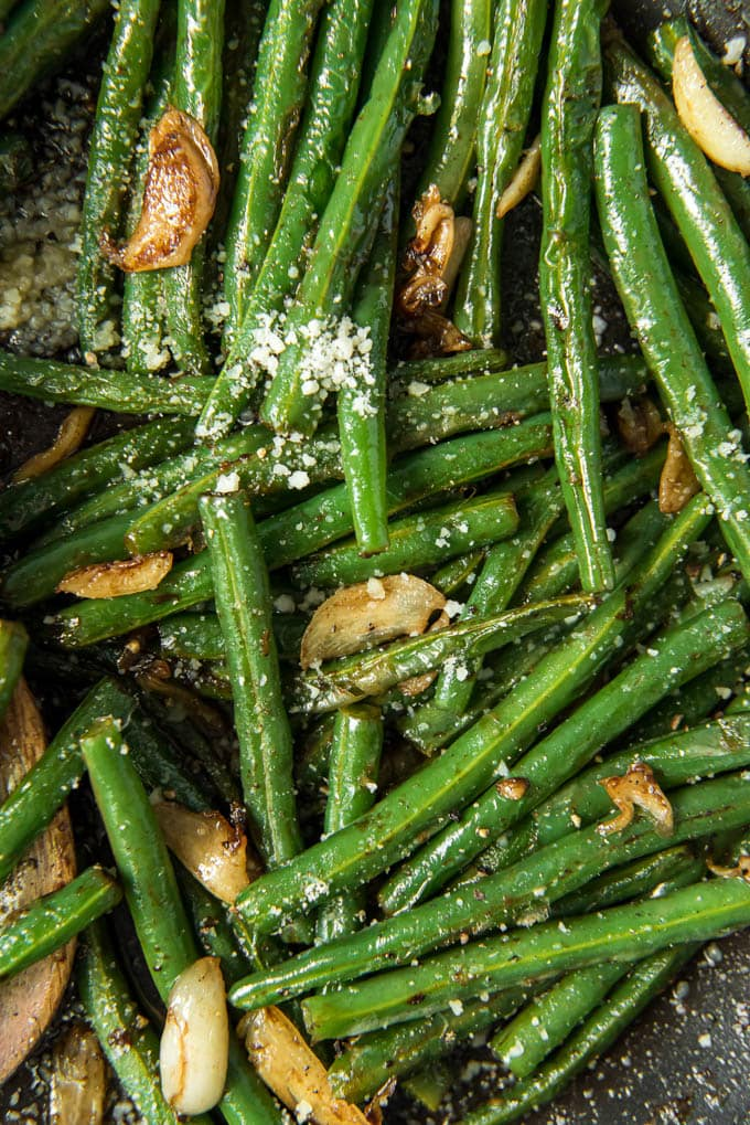 A close up overhead shot of green beans with garlic and parmesan