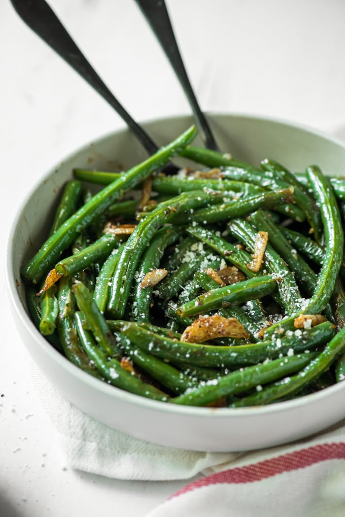 green beans with garlic in a white bowl with two serving spoons