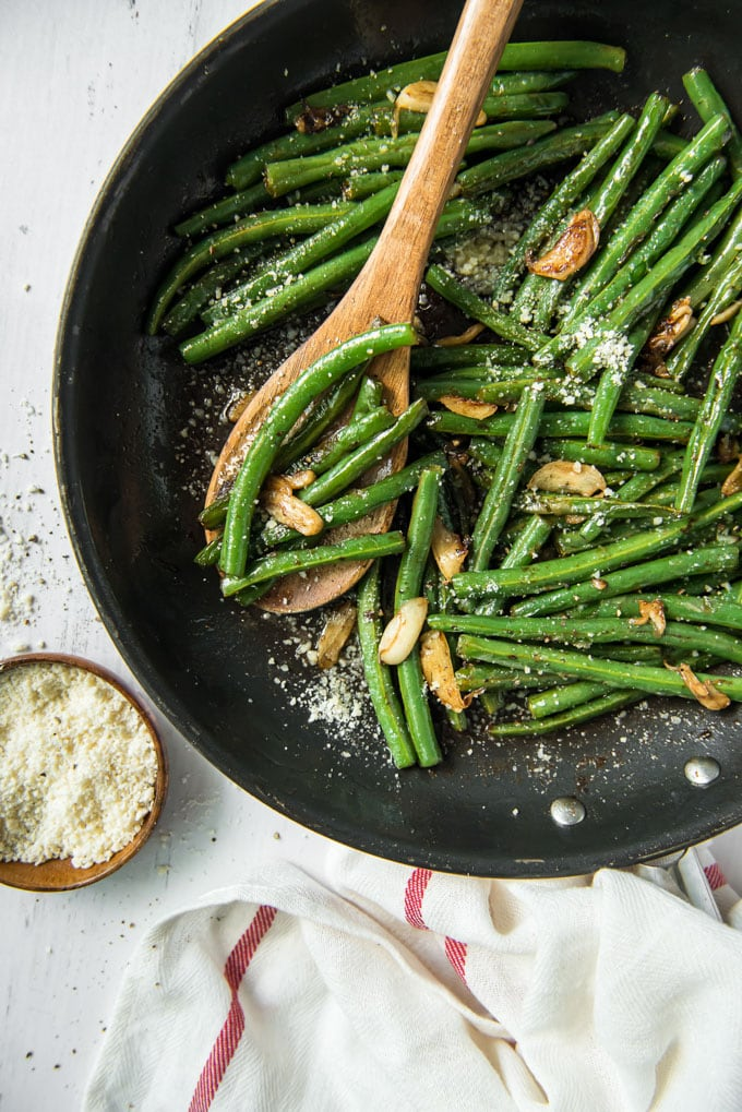 sauteed green beans with garlic and parmesan in a skillet with a wooden spoon