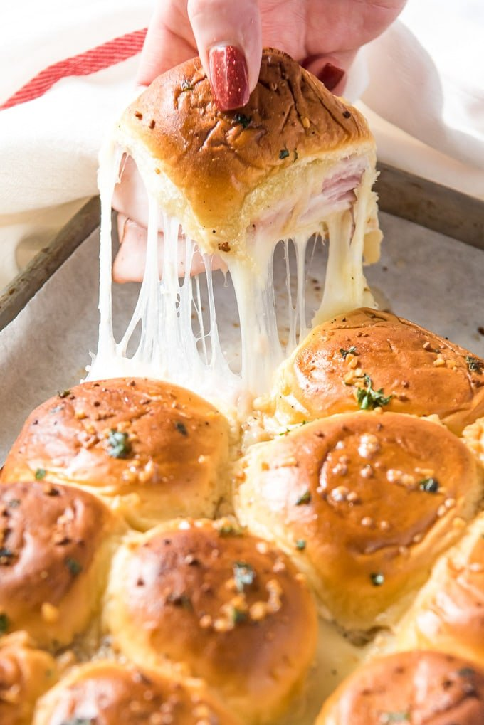 a hand reaching in and pulling out a ham and cheese slider with strings of melted cheese