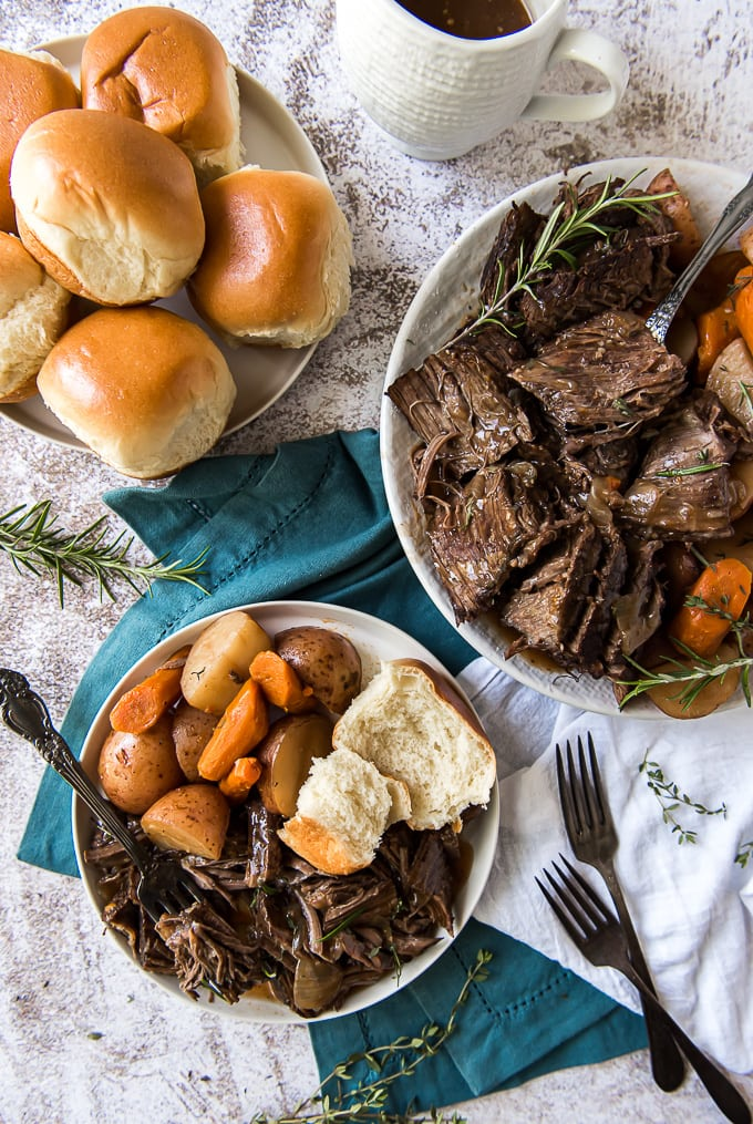 An overhead image of a plate 3 plates containing pot roast, veggies and rolls.