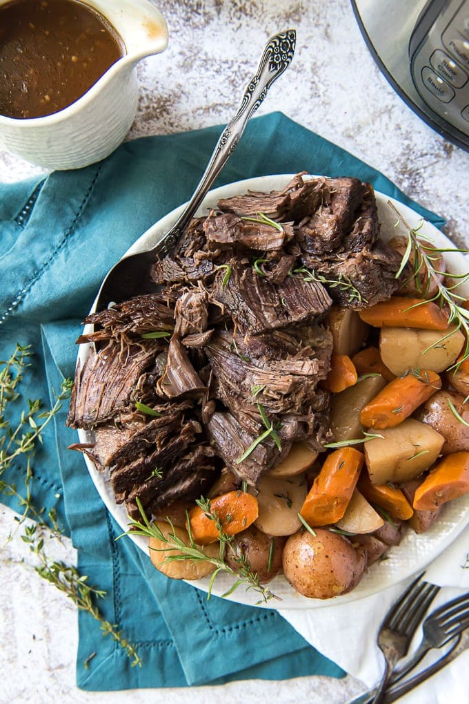 An overhead image of instant pot pot roast on a plate with carrots, potatoes and gravy.